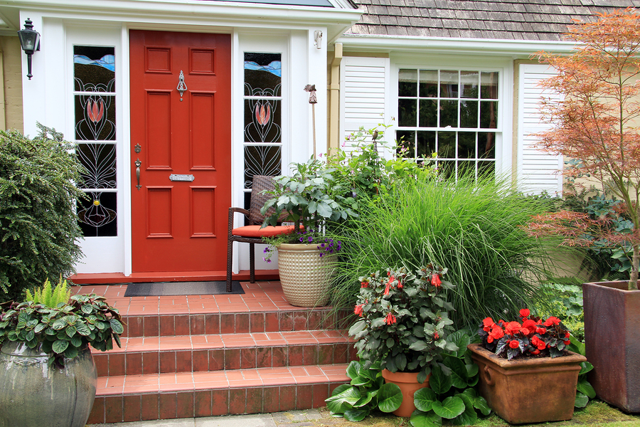 Charming small home with red front door and summer garden containers filled with annual flowers. Pho: Charming small home with red front door and summer garden containers filled with annual flowers. Photo taken from the public sidewalk.