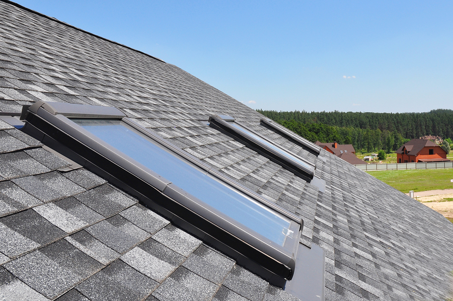 Attic skylight. Asphalt Shingles House Roofing Construction with Attic Roof windows skylights waterproofing.