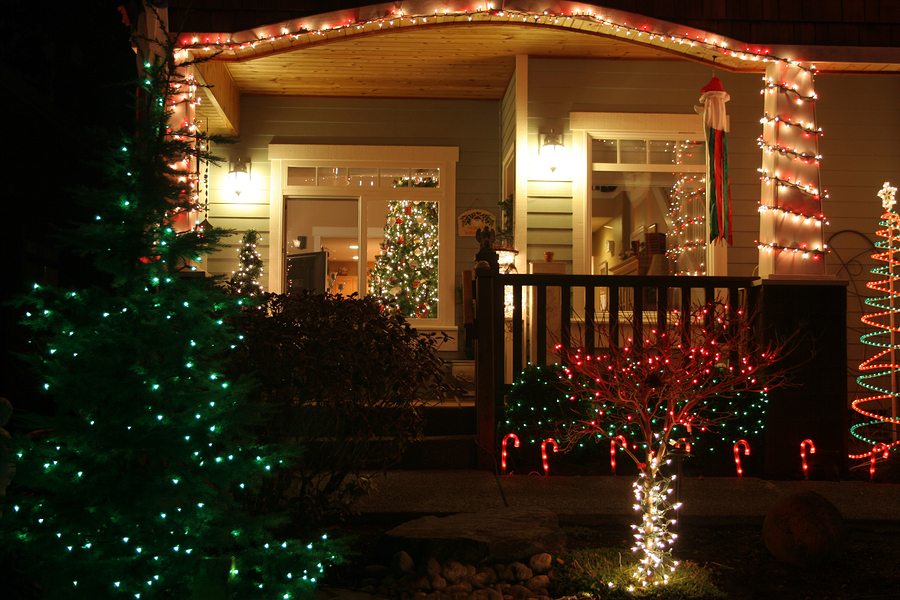 Happy Holidays: the front entry of a house lit up by Chrismas lights at night